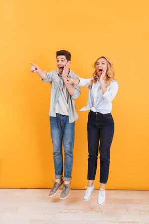 Full length image of surprised man and woman screaming in happiness while pointing fingers aside at copyspace isolated over yellow background