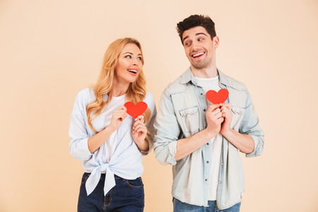 Portrait of lovely couple man and woman in basic clothing looking at each other with smile and holding two red paper hearts isolated over beige background