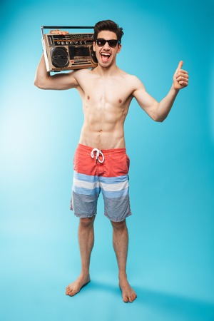 Full length portrait if a cheerful shirtless man in swimming shorts holding tape recorder and showing thumbs up over blue background Stock Photo