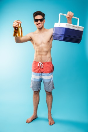 Full length portrait if a cheerful shirtless man in swimming shorts holding cooler bag and beer bottles over blue background Stockfoto - 103775098