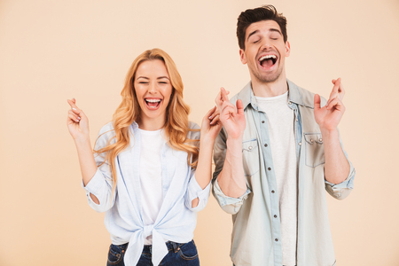 Portrait of caucasian people man and woman in basic clothing squinting eyes with keeping fingers crossed and begging for luck isolated over beige background