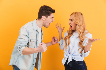 Photo of furious man and woman in denim clothes screaming at each other standing face to face isolated over yellow background