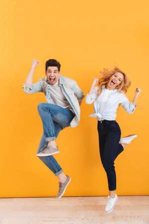 Full length photo of happy young couple screaming in surprise while jumping and clenching fists like winners isolated over yellow background