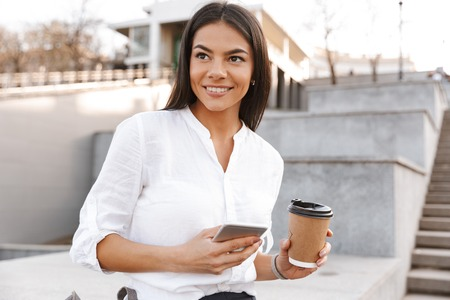 Smiling brunette woman in shirt sitting outdoors and looking away while holding smartphone and cup of coffee