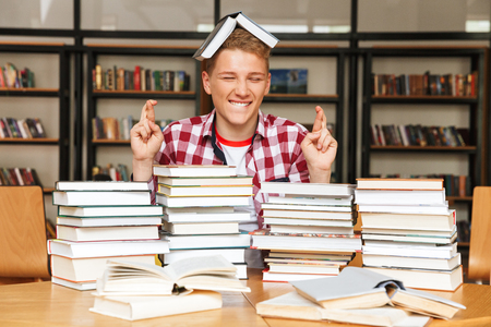 Smiling teenage boy sitting at the library table with big stacks of books and holding fingers crossed for good luck