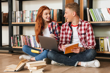Cheerful teenage couple sitting on a floor at the bookshelf in a library and doing homework with laptop computer