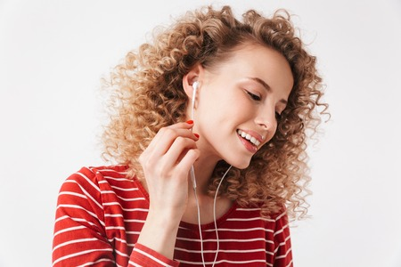 Pleased blonde curly woman in casual clothes and earphones listening music over grey background