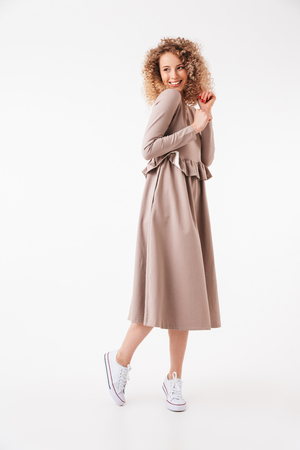 Full length image of Happy blonde curly woman in dress posing and looking away over grey background