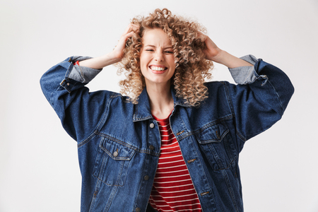 Portrait of a cheerful young girl in denim jacket posing and looking at camera isolated over white background