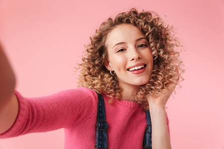 Portrait of happy young girl with curly hair taking a selfie isolated over pink background