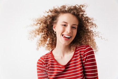 Close up portrait of smiling young girl with curly hair looking at camera isolated over white background
