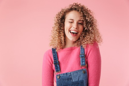 Close up portrait of smiling young girl with curly hair winking and looking at camera isolated over pink background