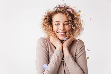Portrait of a cheerful young curly blonde girl in dress playing with colorful confetti isolated over white background Stockfoto