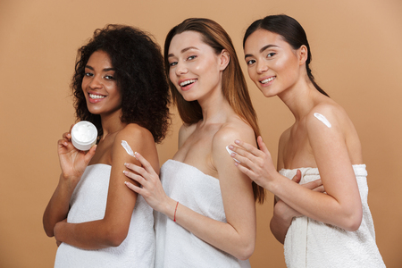 Beauty portrait of three young multiracial women with different types of skin: caucasian, african american and asian girls applying cream on body together isolated over beige background