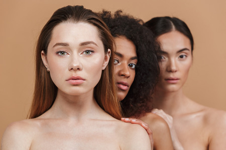 Beauty portrait of three nude women of different nation: caucasian, african american and asian girls standing together isolated over beige background