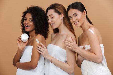 Schoonheidsportret van drie jonge multiraciale vrouwen met verschillende huidtypes: Kaukasische, Afrikaanse Amerikaanse en Aziatische meisjes die room op lichaam samen toepassen die over beige achtergrond wordt geïsoleerd