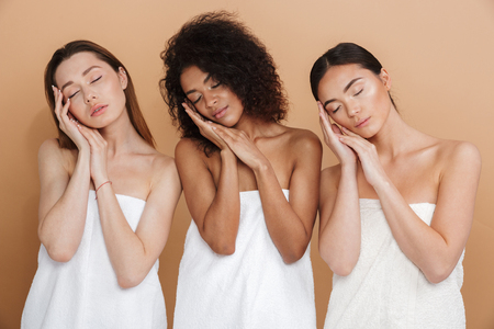 Three beauty sensual women wearing in towels posing with arms together near face and closed eyes over beige background