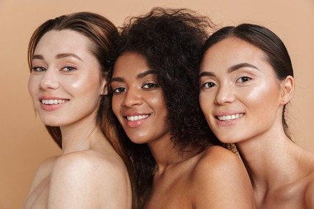 Close up image of Three Smiling naked woman posing together and looking at the camera over beige background