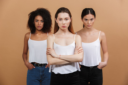 Image of three international women: caucasian, african american and asian girls in casual clothing looking at camera with strict gaze isolated over beige background
