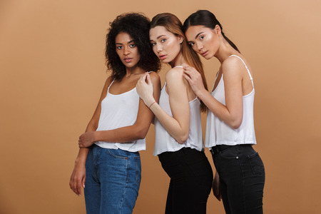 Image of three beautiful women of different nation: caucasian, african american and asian girls in basic clothing standing together isolated over beige background