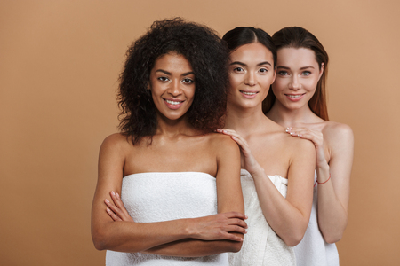 Three smiling multiethnic women wearing in towels posing together and looking at the camera over beige background Stock Photo