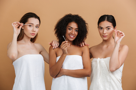 Three pleased naked women wearing in towels using cotton sticks to clean faces while looking at the camera over beige background