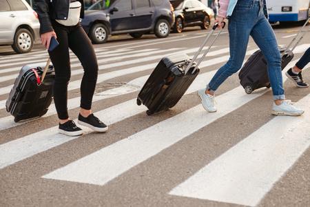 Cropped image of three women walking across pedestrian crossing and carrying luggage after arrival to airport. Air travel or holiday concept 스톡 콘텐츠 - 104161151