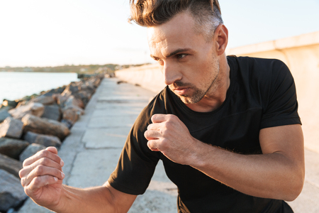Image of strong sportsman boxer make sport boxing exercises outdoors at the beach early morning. Standard-Bild - 104090021