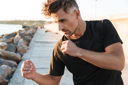 Photo of concentrated sportsman boxer make sport boxing exercises outdoors at the beach early morning. Standard-Bild - 104362090