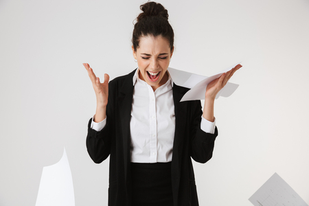 Portrait of an angry young businesswoman screaming and throwing papers isolated over white background Stock Photo