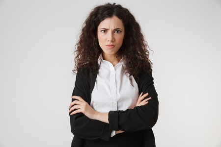 Portrait of an upset young businesswoman standing with arms folded and looking at camera isolated over white background
