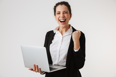 Portrait of an excited young businesswoman holding laptop and celebrating success isolated over white background