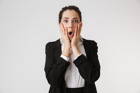 Portrait of a shocked young businesswoman holding arms at her face isolated over white background Stock fotó