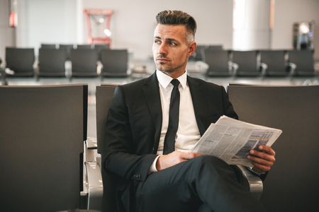 Serious businessman reading newspaper while sitting at the airport terminal lobby Banco de Imagens