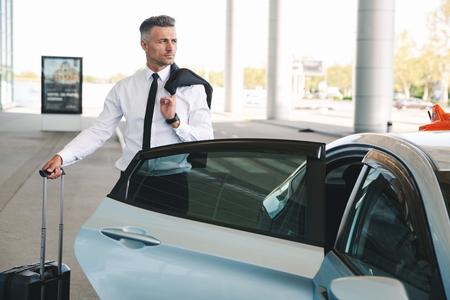 Ernster reifer Geschäftsmann, der außerhalb des Flughafens mit einem Koffer ins Taxi steigt
