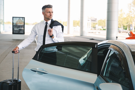 Serious mature businessman getting in taxi outside the airport with a suitcase Stock Photo