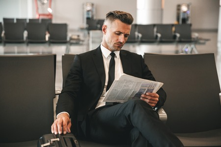 Confident businessman reading newspaper while sitting at the airport terminal lobby