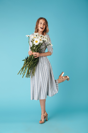 Full length image of Joyful blonde woman in dress having fun with flowers while looking away over blue background Stock Photo