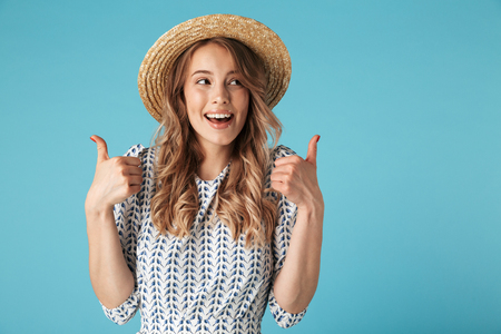 Happy blonde woman in dress and hat showing thumbs up and looking away over blue background Imagens