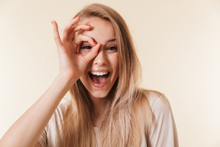 Image of amusing caucasian woman wearing casual clothing laughing and looking at you through hole made by fingers like ok sign isolated over beige background