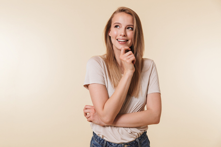 Image of affable blond woman 20s wearing casual t-shirt smiling and looking upward while standing with arms crossed isolated over beige background in studio