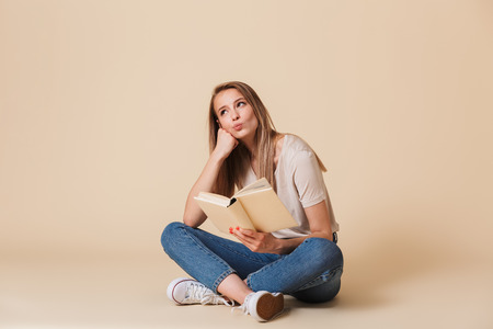 Photo of dreaming woman wearing casual clothing sitting on floor with legs crossed and reading interesting book isolated over beige background