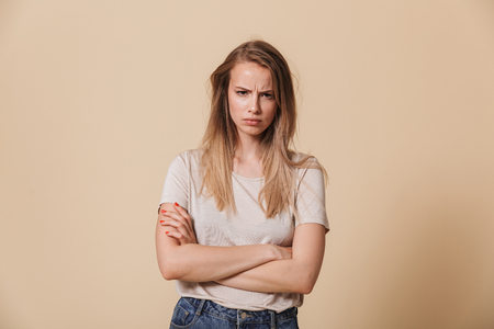 Portrait of an upset casual girl with arms folded isolated over beige background