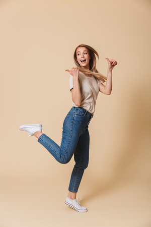 Full length image of pleased blond woman 20s wearing casual clothing running and pointing fingers backward at copyspace isolated over beige background Stock Photo