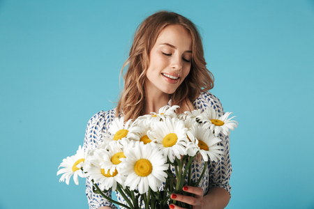 Smiling blonde woman in dress holding bouquet of flowers and enjoys over blue background Banco de Imagens
