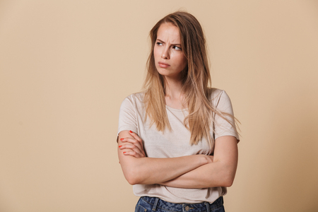 Portrait of an upset casual girl with arms folded looking away isolated over beige background Stock fotó - 104160341