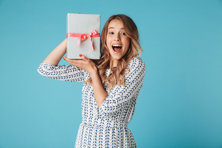 Shocked blonde woman in dress holding gift box while looking at the camera over blue background Stock Photo
