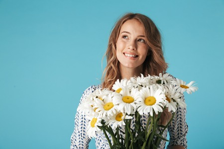Happy blonde woman in dress holding bouquet of flowers and looking up over blue background