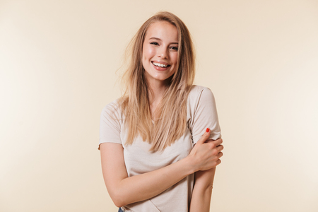 Portrait of beautiful woman 20s with blond hair in basic t-shirt smiling and looking at camera isolated over beige background in studio 写真素材