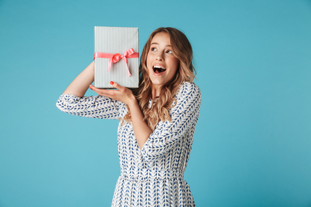 Happy intrigued blonde woman in dress holding gift box near her ear while looking away over blue background Stock Photo